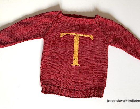 Pullover in rot mit einem aufgestickten gelben T im Maschenstich